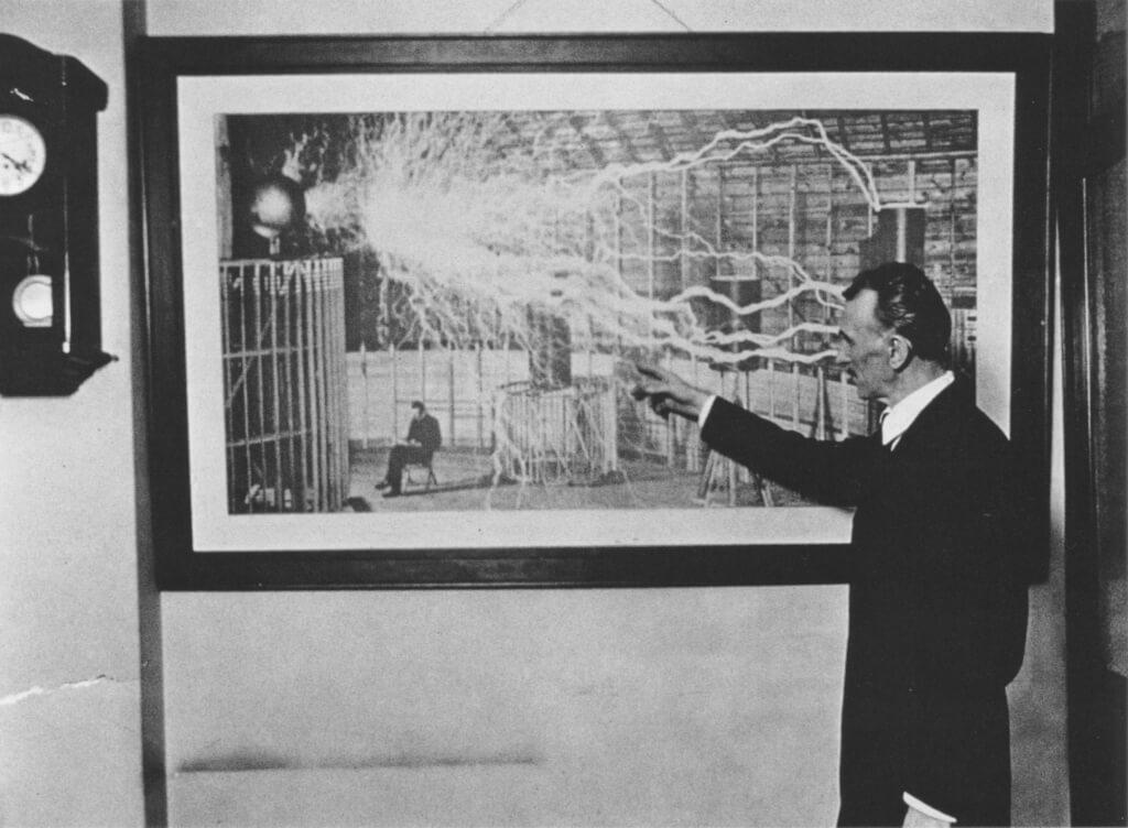 Тесла демонстрирует фотографию своей лаборатории с проходящим по ней разрядом электричества. 1916 год.